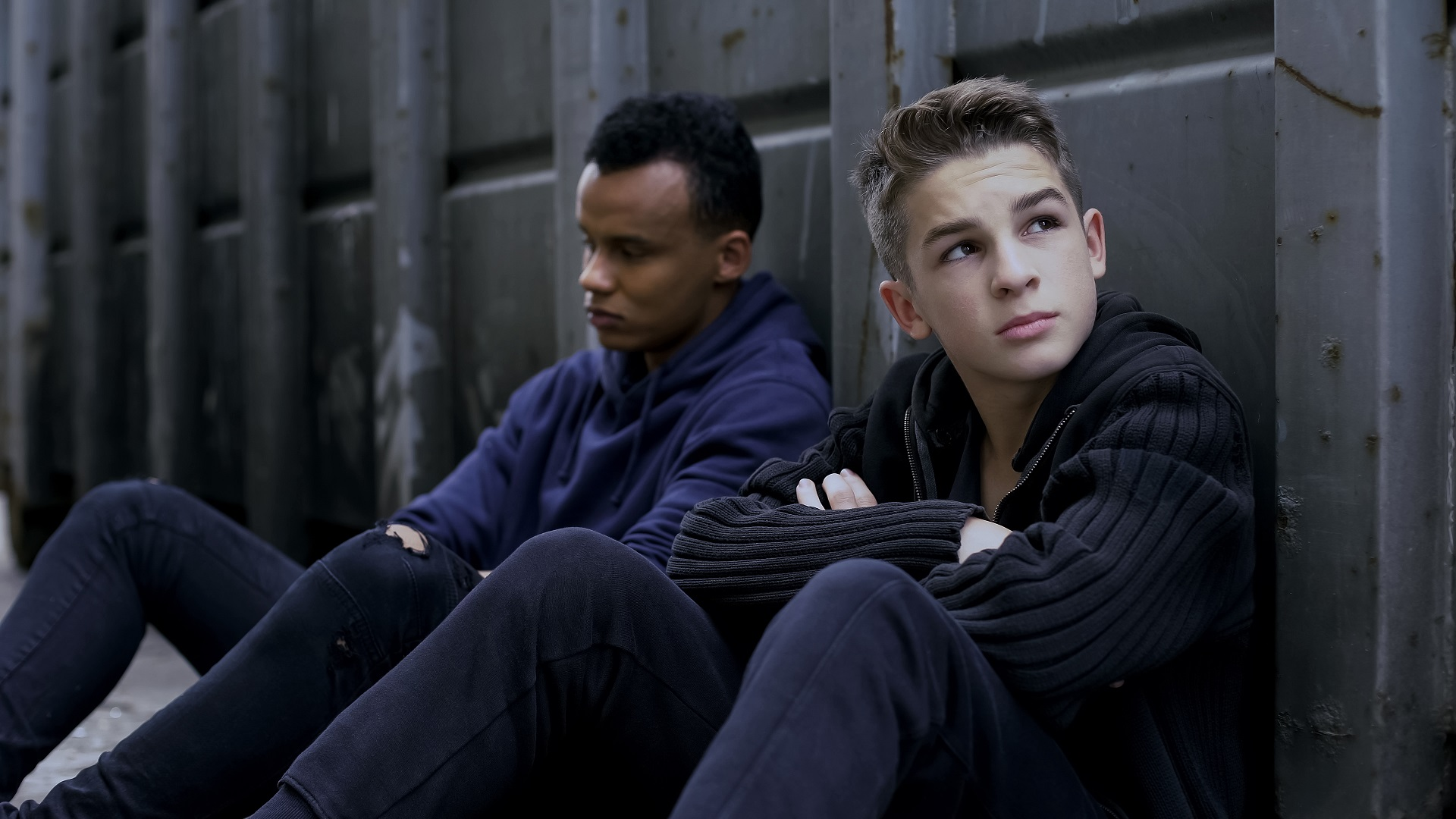 Two teenage boys sitting by a wall